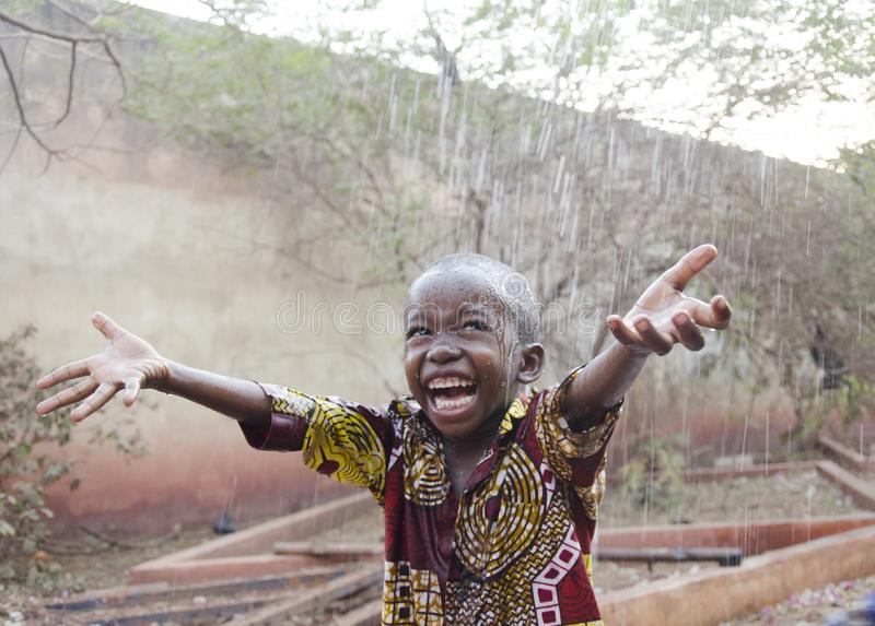 Sweet little African boy under the rain in Mali Africa royalty free stock photography