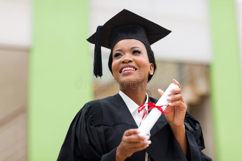 African college student. Pretty african college student in graduation cap and gown in front of school building royalty free stock photography