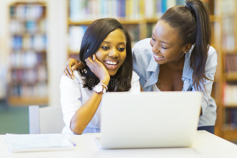 African college students. Cheerful african college students using laptop together