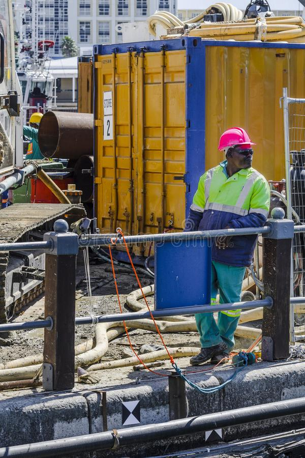 African construction worker Cape Town. African construction worker wearing red safety hat and bright clothing on the dock side of Victoria Albert waterfront Cape royalty free stock photo
