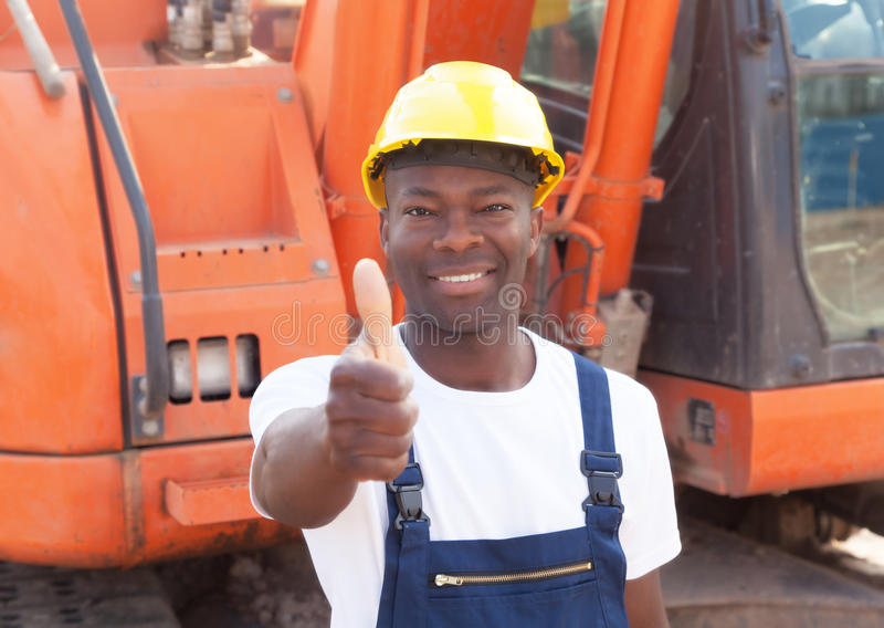 African construction worker with red excavator showing thumb. African construction worker showing thumb with red excavator at construction site in the background stock images