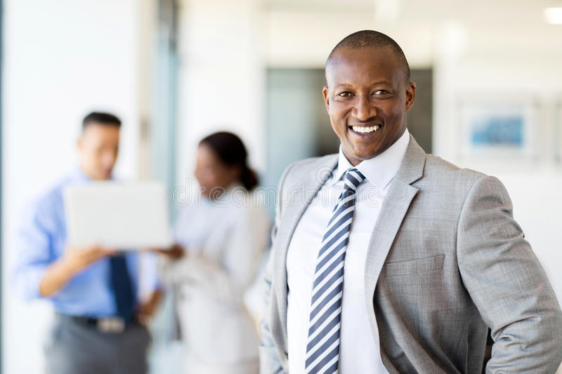 African corporate worker i. Happy african corporate worker in office with colleagues on background royalty free stock photography