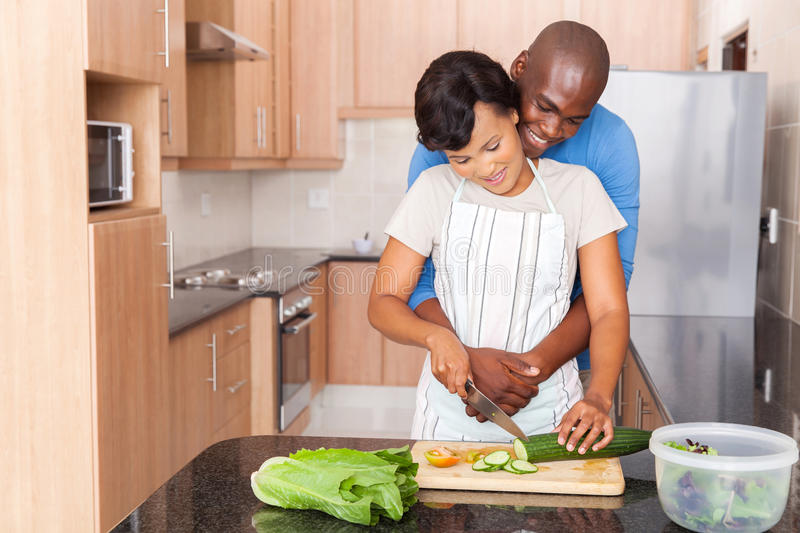 African couple cooking kitchen. Young african couple cooking in kitchen royalty free stock images