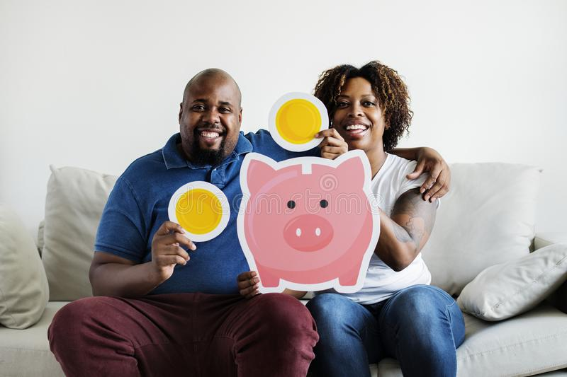 An African couple holding saving money icons home family saving investment concept royalty free stock image