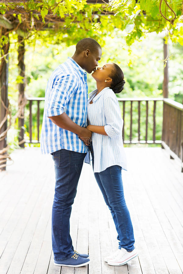 African couple kissing stock images