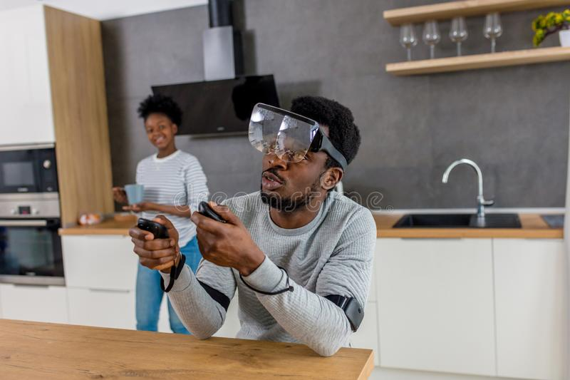 African couple play video games wearing virtual reality glasses at home stock photography