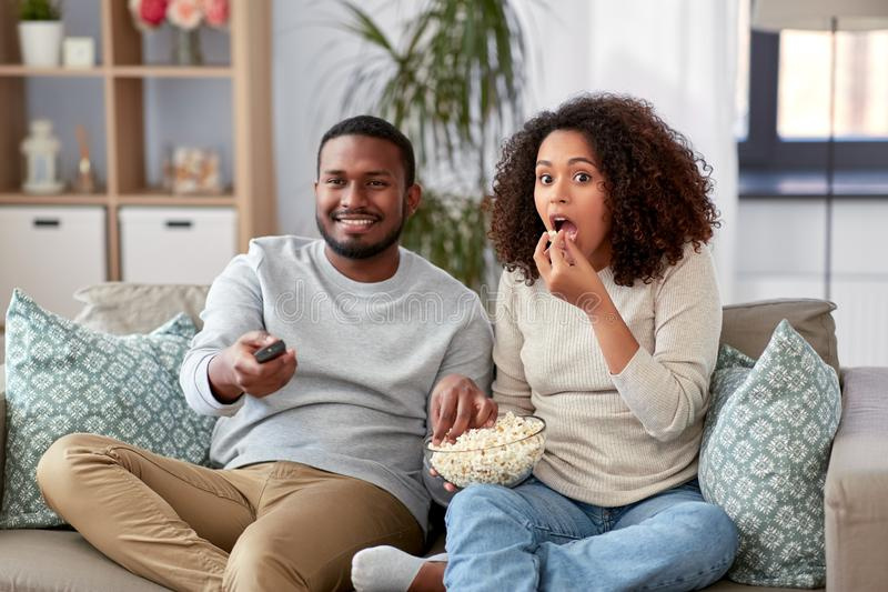 African couple with popcorn watching tv at home royalty free stock photo