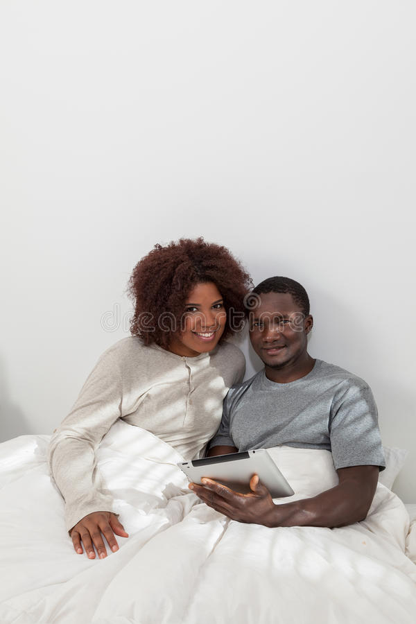African couple using the computer. Black couple in love using the ipad stock photography