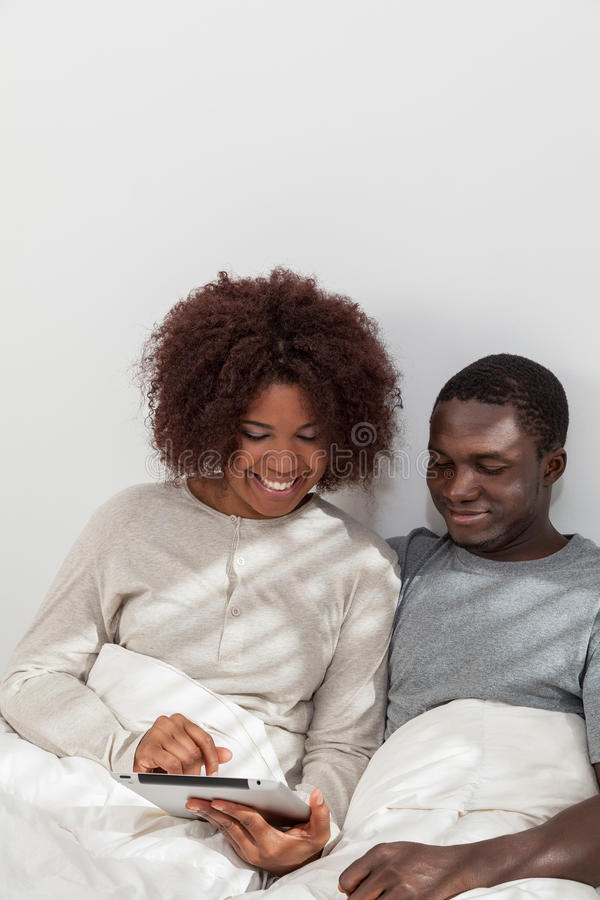 African couple using the computer. Black couple in love using the tablet royalty free stock image