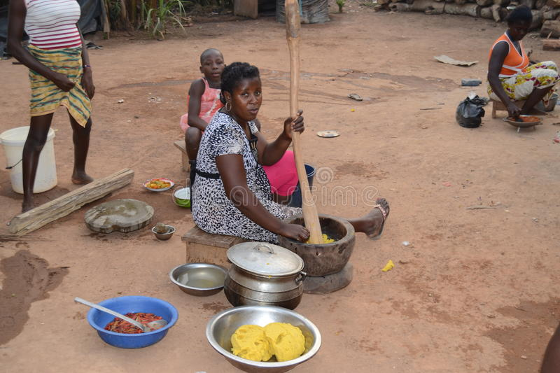 AFRICAN CUISINE. Image of an African family cooking for the guests in solidarity on the floor to celebrate a joyful event without worrying about the risks that royalty free stock photos