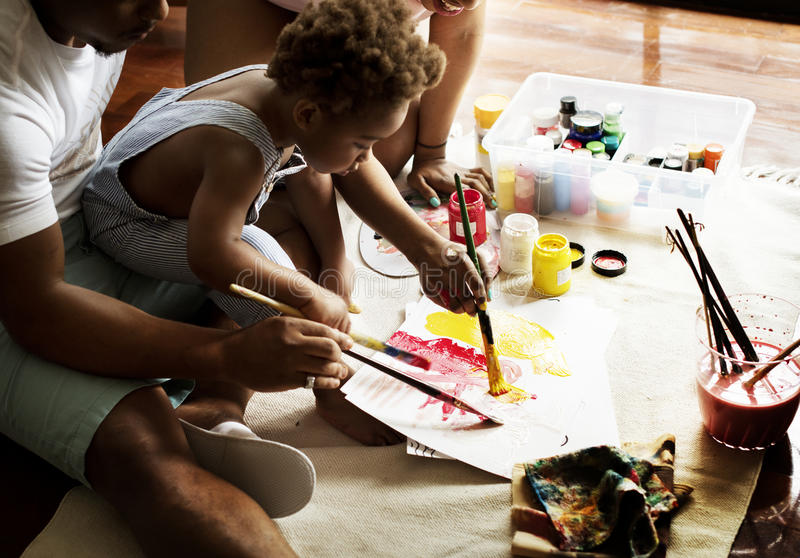 African descent dad teaching his child how to paint royalty free stock photos