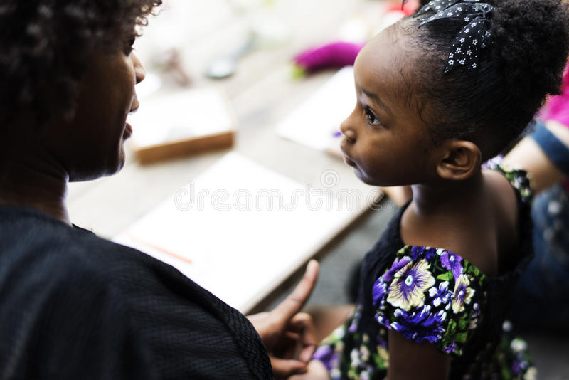 African descent girl is listening to her teacher royalty free stock image