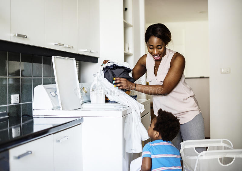 African descent kid helping mom doing the laundry royalty free stock photos