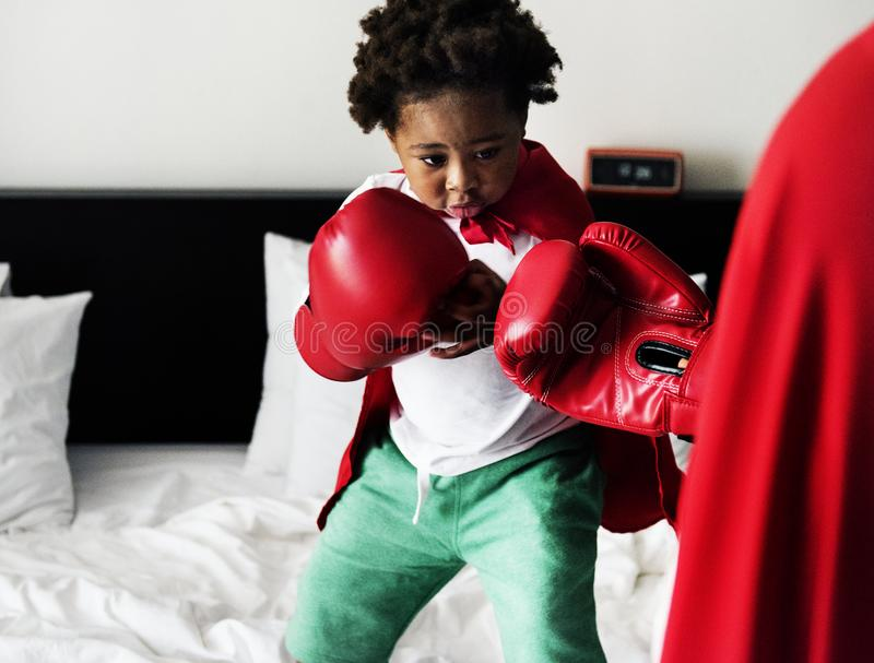 African descent kid wearing robe doing boxing with dad on the be royalty free stock image
