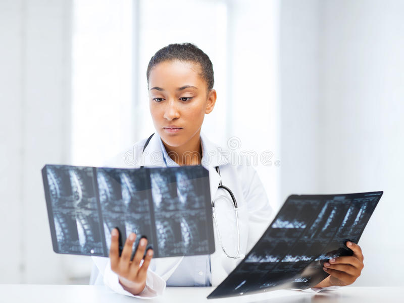 African doctor looking at x-rays. Healthcare, medical and radiology concept - african doctor looking at x-rays royalty free stock photos