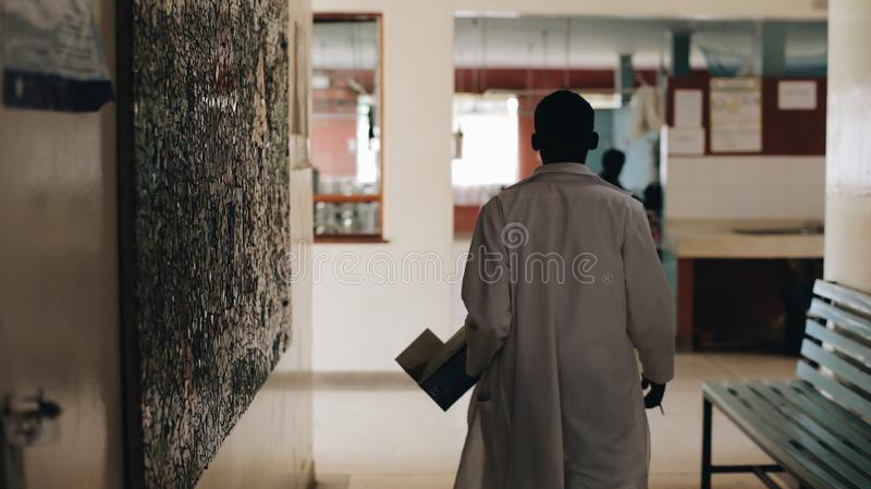 African doctor in white medical gown walking through the hospital lobby in village in Africa. royalty free stock photography