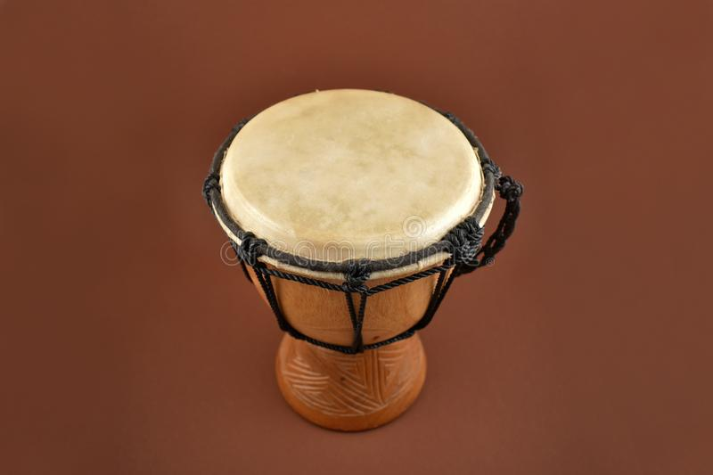 African drum stock images. Wooden drum with goat skin, ethnic musical instrument. Djembe Drum on a brown background stock photography