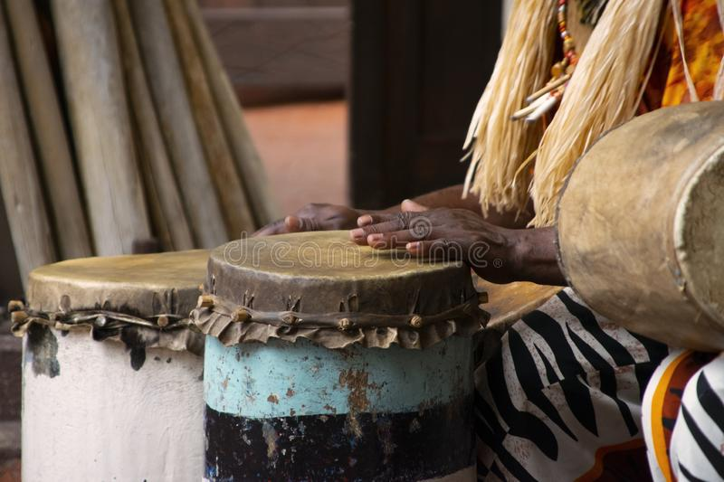 A African Drummer playing on a drum in day time. stock photo