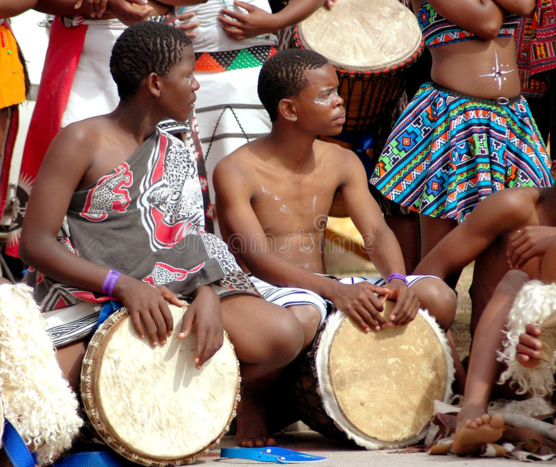African drummers. Two black African drummers in traditional clothing performing in front of a group on the street outdoors. Entertainment at Ironman South Africa royalty free stock photo