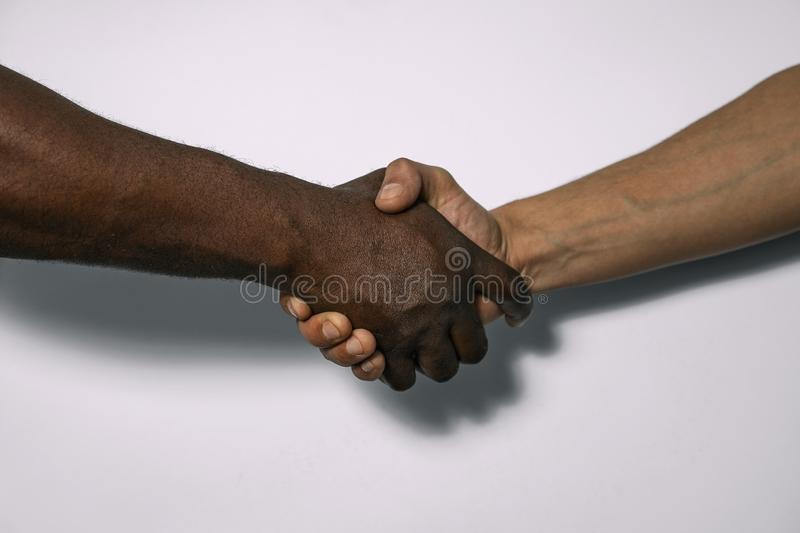 African and European handshake as a sign of friendship, greeting, agreement or deal.  stock photos