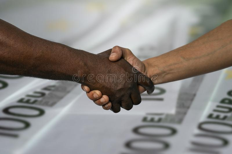 African and European handshake as a sign of friendship, greeting, agreement or deal,against the background of 100 euro banknotes.  royalty free stock photos