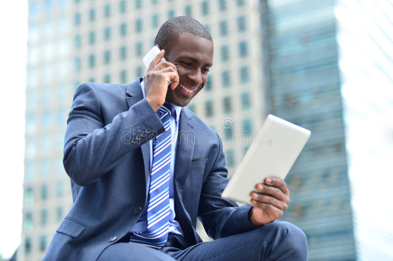 African executive with tablet pc and cellphone royalty free stock photos