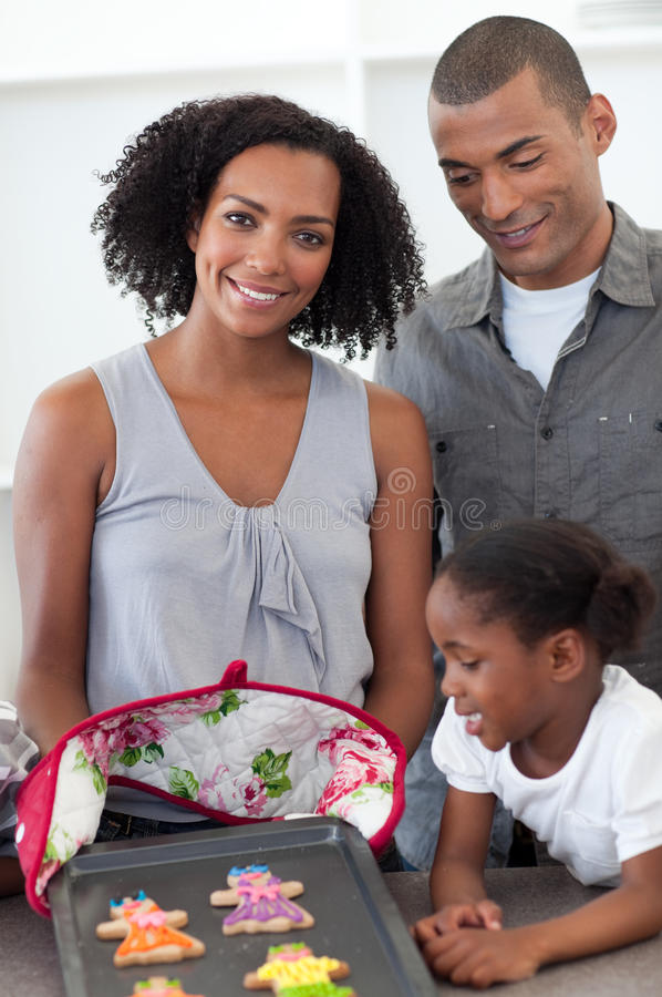 African family showing handmade cookies. In the kitchen with mother smiling to the camera royalty free stock photo