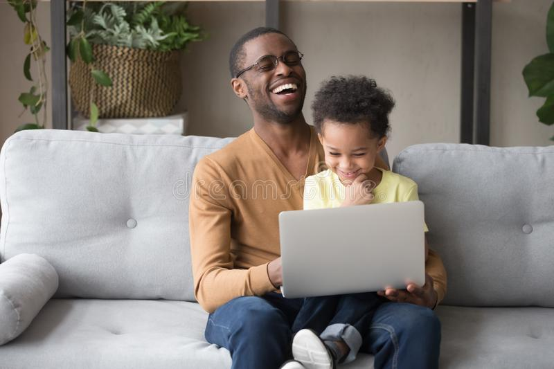 African father and cute kid son having fun with computer. Happy black dad watching funny cartoons movie with little toddler son sitting on couch, african father royalty free stock photos