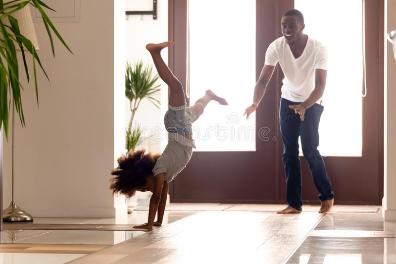 Active african little girl showing to father making handstand position royalty free stock photo