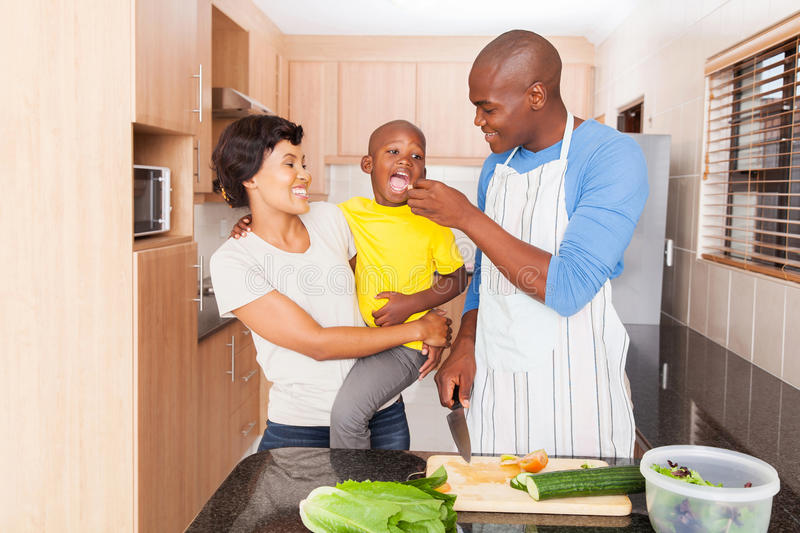African father feeding son. Loving african father feeding son a piece of tomato in kitchen royalty free stock photos