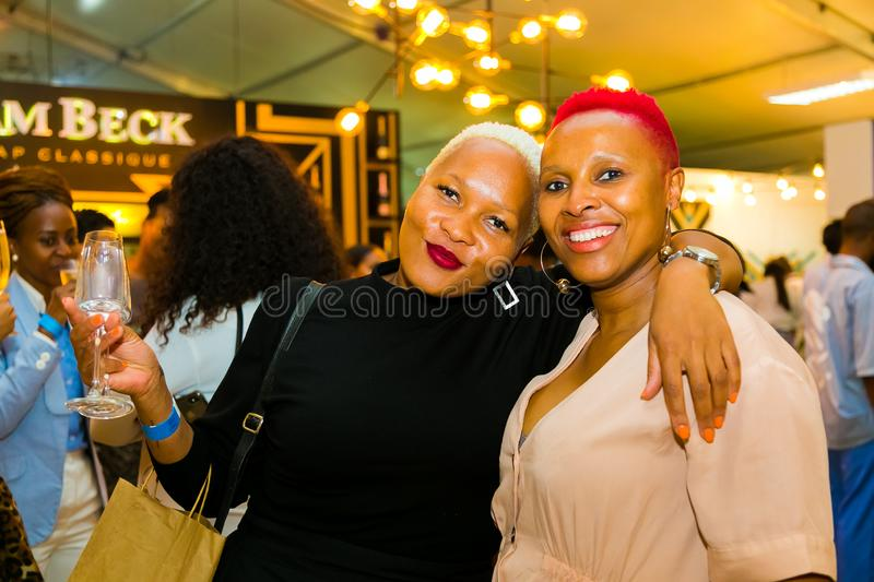 African Female Friends eating, drinking and generally enjoying a day out at a Food and Wine Fair. Johannesburg, South Africa - October 11 2018: African Female royalty free stock image