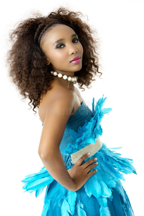 African Female Model Wearing Turquoise Feathered Dress, Big Afro, Sideways royalty free stock image