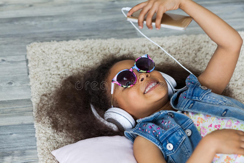 African gil at home. Cute African girl at home, listening to music in big white headphones, Lies on the floor stock photos