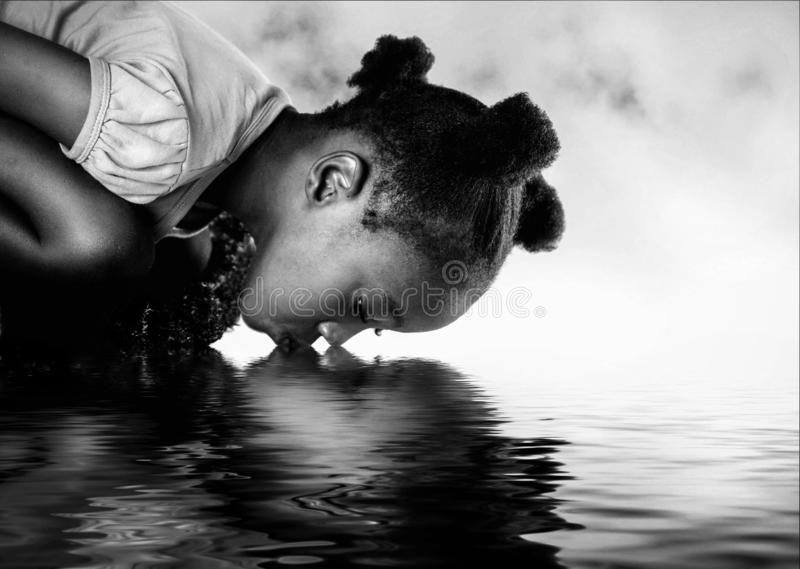 African girl drinking from a river. royalty free stock photos