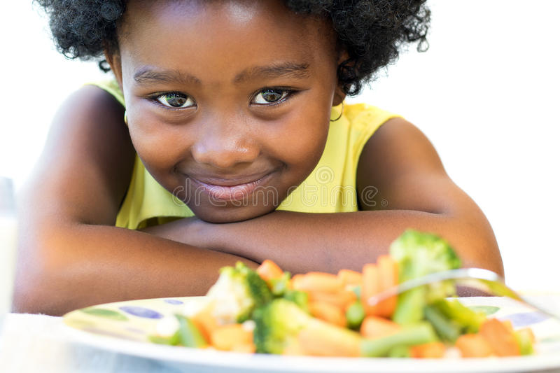 African girl in front of vegetable dish. Close up face shot of cute African girl in front of healthy vegetable dish. Isolated on white royalty free stock photography