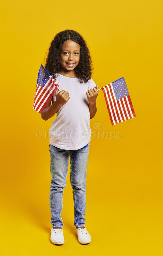 African girl holding American flags. Portrait of African girl holding American flags royalty free stock image