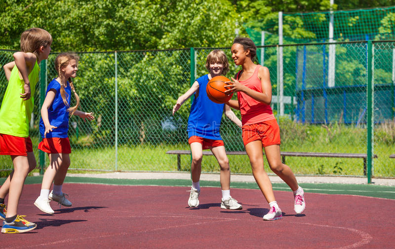 African girl holds ball and teens play basketball stock images