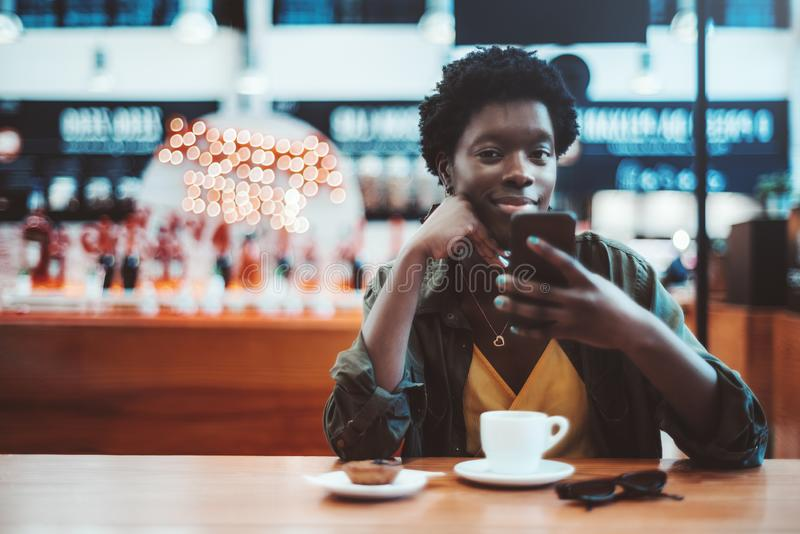 African girl in an indoor cafeteria. A cheerful young black woman with short Afro hair is chatting with her friend via the cellphone while sitting indoors of a stock image