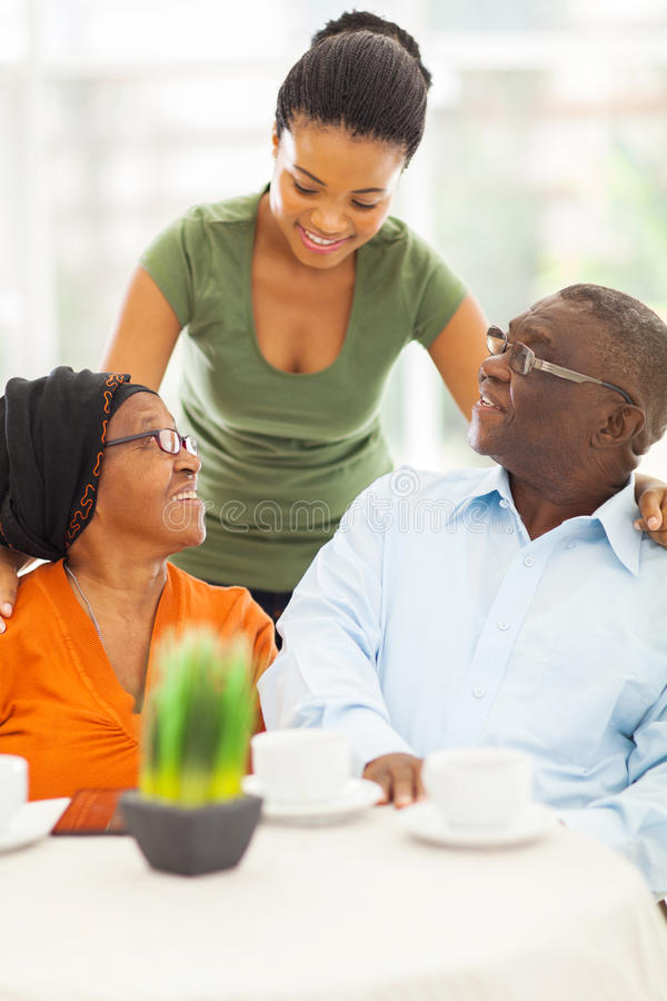 African girl senior parents. Beautiful african girl talking to senior parents at home royalty free stock images
