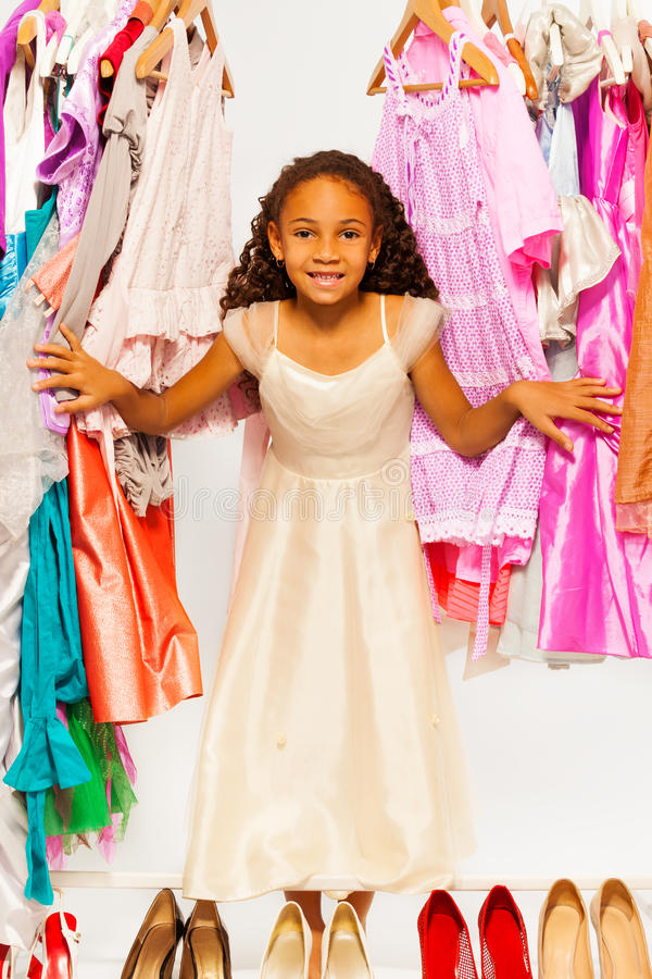 African girl during shopping stands among dresses. Cute African girl during shopping standing between hangers with colorful bright dresses, clothes and high royalty free stock photography