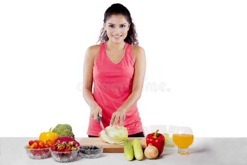 African girl preparing healthy salad on studio royalty free stock photo
