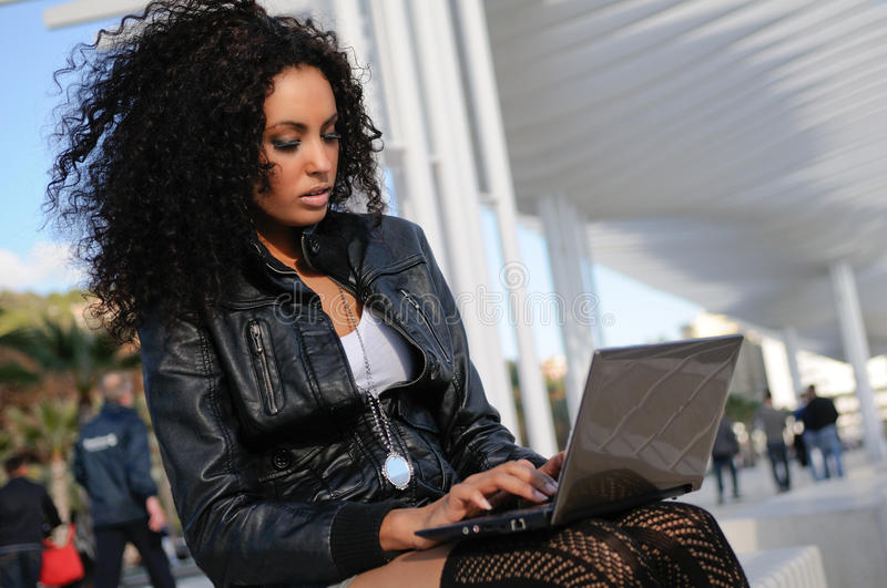 African girl using a laptop in the street stock photos