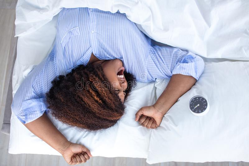 African girl waking up at the weekend. Top view photo. copy space,tiredness, exhaustion royalty free stock images