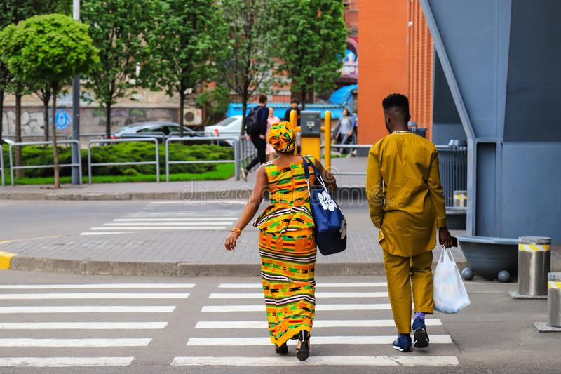 African girl and young man in bright yellow national clothes with bags go after shopping along the street. Dnepropetrovsk royalty free stock photos