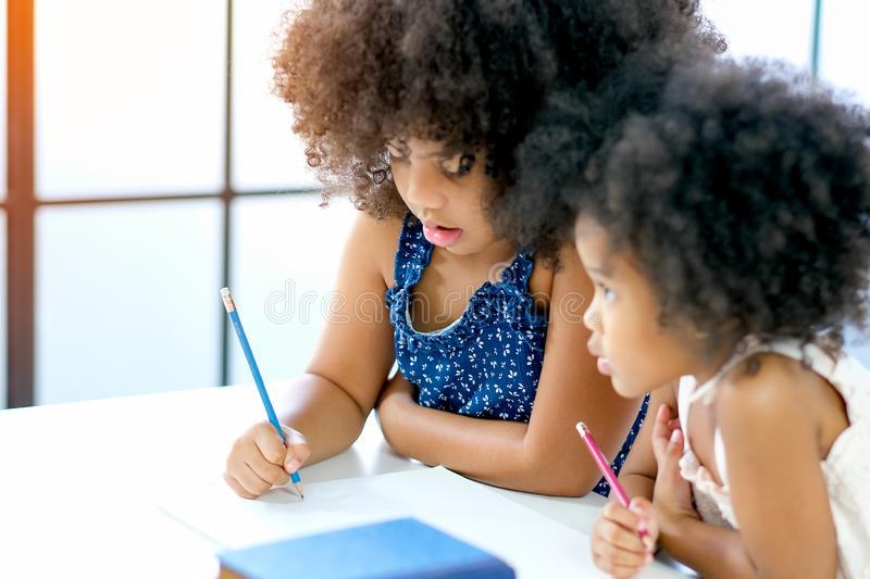 African girls as older and younger sister write or draw something on white paper near the book in front of glass windows with day. Light royalty free stock photo