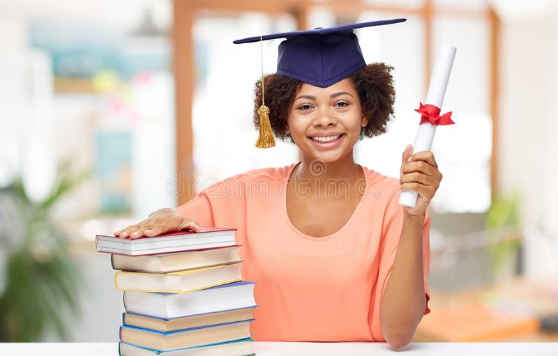 African graduate student with books and diploma. Education, graduation and knowledge concept - happy smiling african american graduate student girl in bachelor royalty free stock image