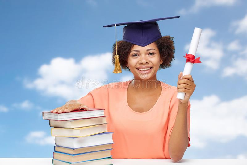 African graduate student with books and diploma. Education, school, knowledge and graduation concept - happy smiling african american graduate student girl in stock photography