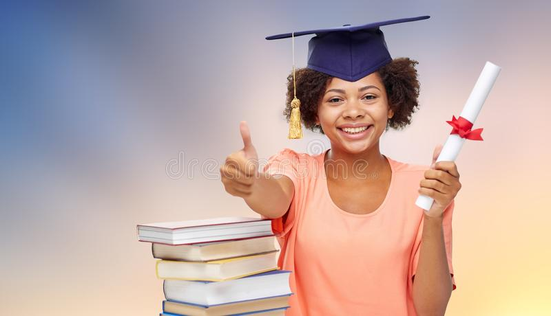 African graduate student with books and diploma. Education, school, knowledge and graduation concept - happy smiling african american graduate student girl in royalty free stock photo