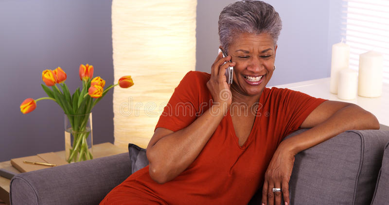 African grandmother talking on smartphone. Black grandmother talking on smartphone royalty free stock photo