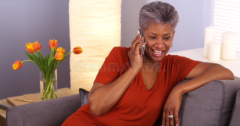 African grandmother talking on smartphone. Happy African grandmother talking on smartphone royalty free stock images
